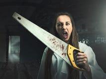Retrato asustadizo de una mujer enojada con una sierra fotos de archivo libres de regalías