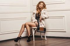 Retrato atractivo de la mujer hermosa joven en las botas de cuero y bolso elegante Foto de archivo libre de regalías