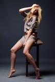 Retrato atractivo de la mujer joven que se sienta en silla Fotografía de archivo libre de regalías