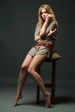 Retrato atractivo de la mujer joven que se sienta en silla Foto de archivo