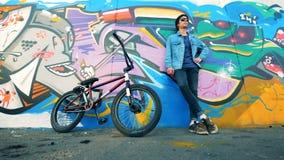 Retrato atractivo del adolescente El ciclista masculino joven se coloca cerca de una pared con una bici almacen de video