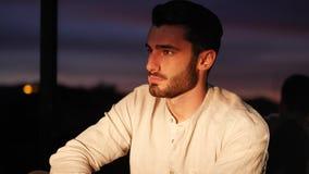 Retrato atractivo del hombre joven en la puesta del sol