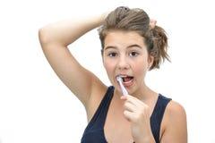 Retrato bastante de la sonrisa adolescente cepillando sus dientes aislados en el fondo blanco Imagen de archivo libre de regalías