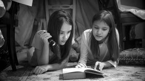 Retrato blanco y negro de dos adolescentes que mienten en el libro del piso y de lectura con la linterna Foto de archivo libre de regalías