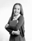 Retrato blanco y negro de la colegiala sonriente que presenta con el libro Fotos de archivo libres de regalías