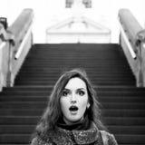 Retrato blanco y negro de la morenita asombrosa con la boca abierta que mira la cámara Escaleras en el fondo Imagen de archivo