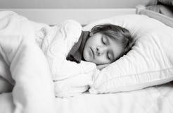 Retrato blanco y negro de la muchacha en suéter que duerme en cama Foto de archivo