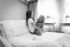 Retrato blanco y negro de la muchacha linda que se sienta en cama y el abrazo Fotos de archivo libres de regalías