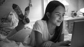 Retrato blanco y negro de la muchacha sonriente linda en los pijamas que mienten en cama con el ordenador portátil Imágenes de archivo libres de regalías
