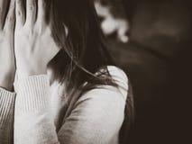 Retrato blanco y negro de la mujer joven triste que se sienta por el sofá Foto de archivo