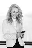 Retrato blanco y negro de la mujer sonriente que usa el teléfono móvil Imagenes de archivo