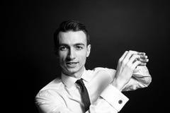 Retrato blanco y negro de un hombre de negocios joven en una camisa blanca y un lazo negro, hablando y explicando imágenes de archivo libres de regalías