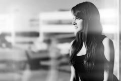 Retrato blanco y negro de una salida que espera de la mujer para en el aeropuerto fotos de archivo