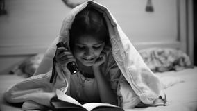 Retrato blanco y negro del adolescente sonriente con el libro de lectura de la antorcha Imagen de archivo