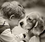 Retrato blanco y negro del muchacho y del perro Foto de archivo libre de regalías