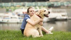 Retrato blanco y negro emocional de una muchacha sola triste que abraza su perro fotografía de archivo