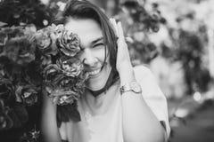 Retrato blanco y negro hermoso de la mujer joven morena sensual en el vestido blanco cerca de rosas rojas imagen de archivo libre de regalías