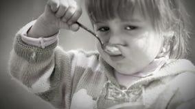 Retrato blanco y negro: La niña linda come con la cuchara almacen de metraje de vídeo