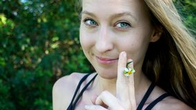 Retrato bonito da erva daninha de fumo da flor da margarida da cara loura nova da mulher que sorri com os olhos claros azuis isol foto de stock