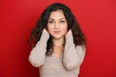 Retrato bonito da jovem mulher com cabelo ondulado longo preto no vermelho Fotografia de Stock Royalty Free