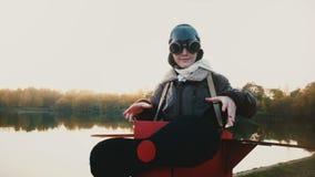 Retrato bonito da menina feliz que põe vidros sobre no traje piloto plano do divertimento que olha o movimento lento da câmera filme