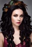 Retrato bonito da mulher Levantamento da jovem senhora isolado no fundo cinzento com as penas no cabelo Imagens de Stock
