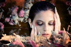 Retrato bonito da mulher na água com folhas de outono imagem de stock royalty free
