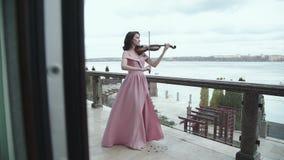Retrato bonito da mulher que joga no violino no balcão filme