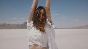 Retrato bonito do estilo de vida da jovem mulher livre feliz que levanta, girando com os braços abertos no lago Utá do deserto de filme
