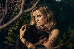 Retrato bonito do modelo da jovem mulher com o gato preto na floresta w imagem de stock