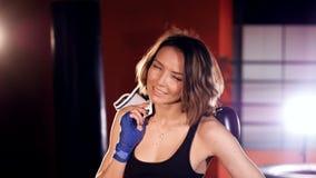 Retrato Boxeador atractivo, satisfecho, sonriente de la mujer en gimnasio del boxeo metrajes