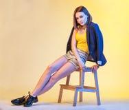 Retrato brilhante colorido da mulher à moda que senta-se em uma cadeira Imagens de Stock