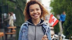Retrato a cámara lenta del viajero afroamericano sonriente de la muchacha que sostiene la bandera canadiense y que mira la cámara almacen de video