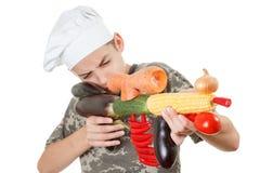 Retrato cômico de um cozinheiro chefe adolescente com vegetais do rifle, fundo branco do menino Foto de Stock