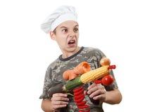 Retrato cômico de um cozinheiro chefe adolescente com vegetais do rifle, fundo branco do menino Imagem de Stock Royalty Free