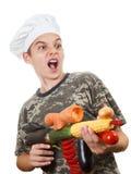 Retrato cômico de um cozinheiro chefe adolescente do menino com vegetais do rifle, elogios gritando Imagens de Stock Royalty Free