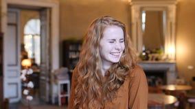 Retrato caucásico de la cara de la mujer del pelo rojo joven en café almacen de video