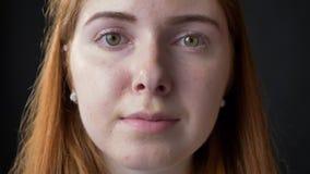 Retrato cercano de la cara hermosa seria joven de la mujer que mira la cámara con la expresión en cuestión y ocupada, negro metrajes