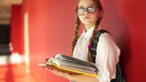 Retrato cercano de la colegiala hermosa con los libros en el pasillo de la escuela La muchacha lleva los vidrios Mirada seria exc almacen de video