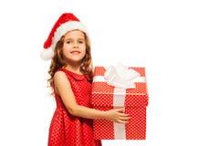 Retrato cercano de la muchacha en presente del control del sombrero de Papá Noel Foto de archivo libre de regalías