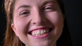 Retrato cercano de la mujer encantadora joven que ríe y que sonríe en la cámara, aislado en fondo negro almacen de video