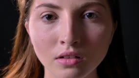 Retrato cercano de la mujer joven seria que mira la cámara, aislado en fondo negro del estudio, referido y concentrado almacen de metraje de vídeo
