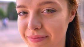Retrato cercano de la mujer tímida joven del jengibre que mira la cámara, calle en el fondo, hembra hermosa que sonríe al aire li almacen de metraje de vídeo