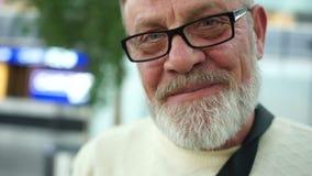 Retrato cercano de un hombre maduro con vidrios y una barba gris Pensionista que sonríe sinceramente en el aeropuerto, compras almacen de video