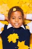 Retrato cercano de un muchacho negro en hojas de otoño Imagen de archivo