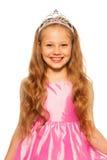 Retrato cercano de una muchacha en vestido rosado con la corona Foto de archivo
