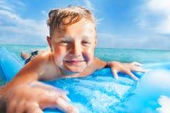 Retrato cercano de una nadada del muchacho en matrass en el mar Foto de archivo libre de regalías