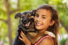 Retrato cercano del adolescente en el abrazo del pequeño perro Imagen de archivo libre de regalías