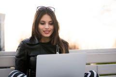 Retrato cercano del estudiante de mujer magnífico del oscuro-pelo que usa el ordenador portátil en el campus, adolescente femenin Imagen de archivo