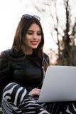 Retrato cercano del estudiante de mujer magnífico del oscuro-pelo que usa el ordenador portátil en el campus, adolescente femenin Fotografía de archivo